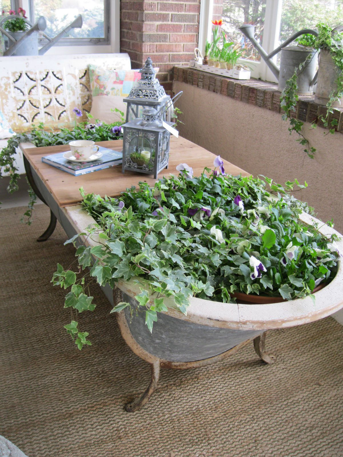An old clawfoot tub wasn't put to waste in this thrift store DIY project - it's multipurpose new life is as a planter and outdoor patio table
