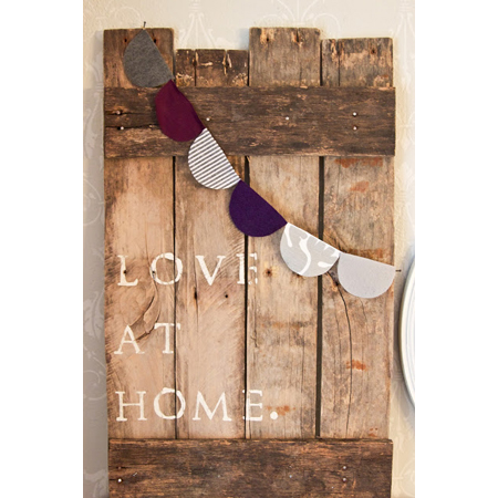 The Winthrop Chronicles made this reclaimed barnwood wall art that's draped with a fabric banner