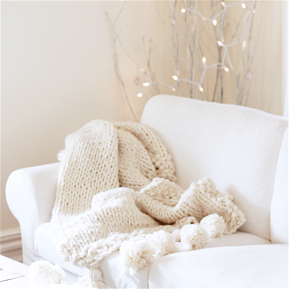 This soft and cozy throw has little pom poms at the end - super adorable!