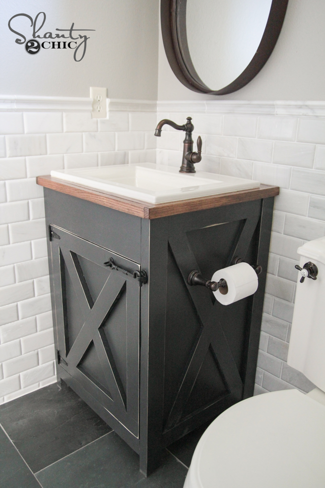 This black vanity with dark stained wood adds an industrial element to this farmhouse bathroom.