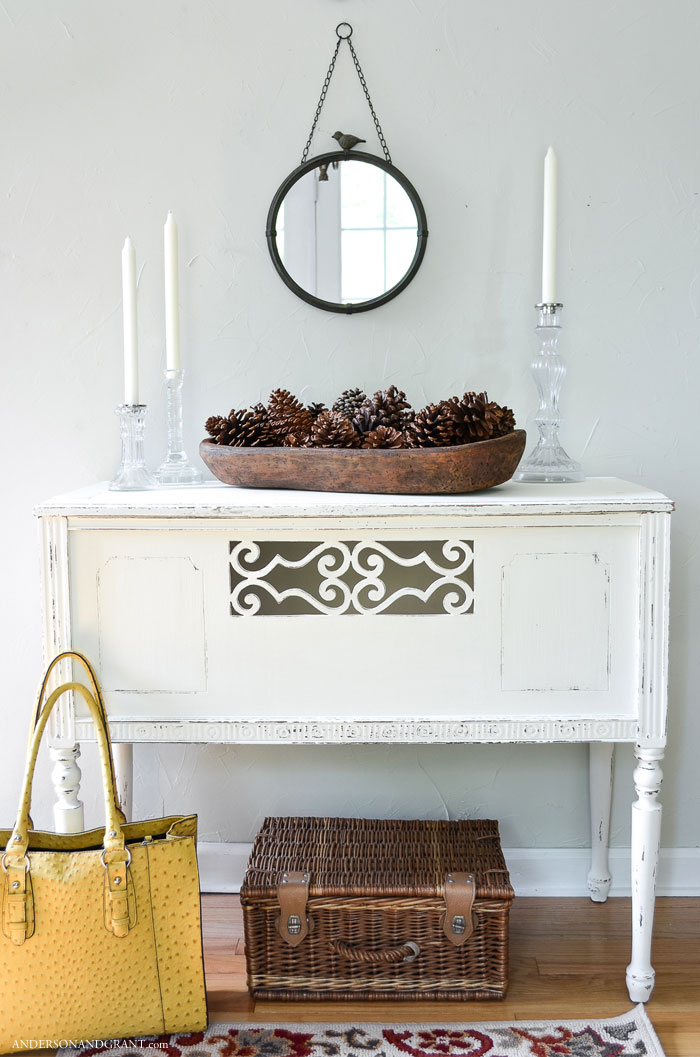 This rustic bowl of pine cones pairs well with the white vintage table.