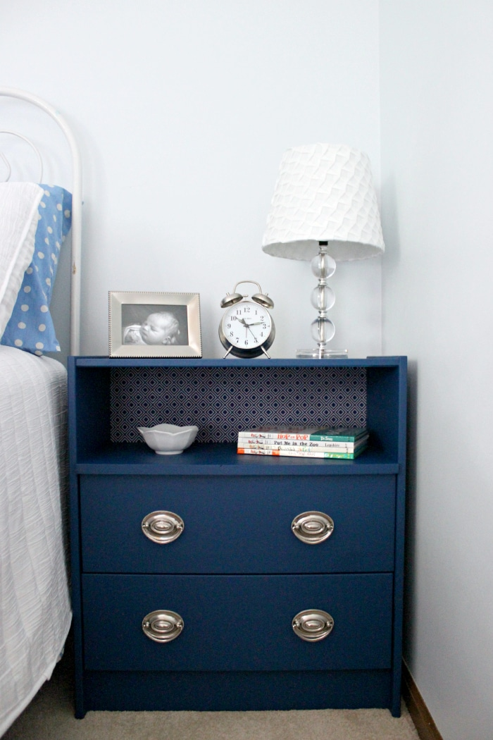This refinished night stand is painted blue and matches the wallpaper accent.
