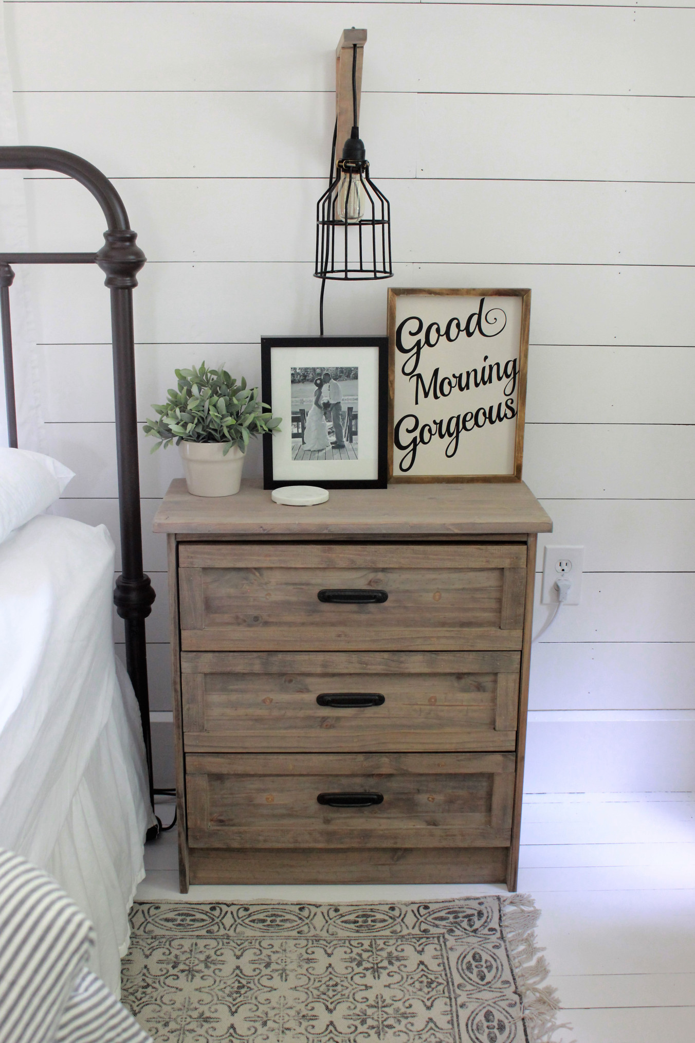 The lightly stained nightstand against the white shiplap wall evokes farmhouse.