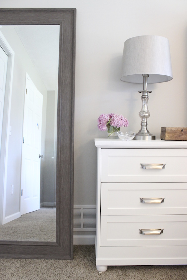 This white nightstand pairs well with the gray mirror and simple decor.