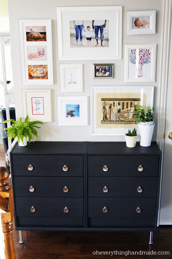 The wall with photos compliments the simple accent table.