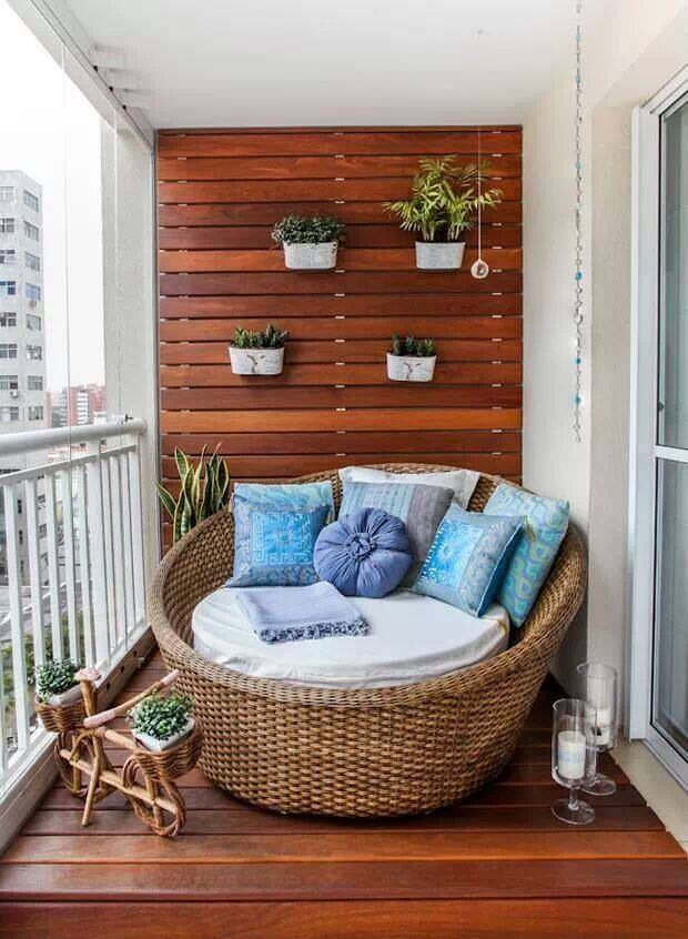 This balcony maximizes the small space with rich wood, small plants, and a comfortable sitting area