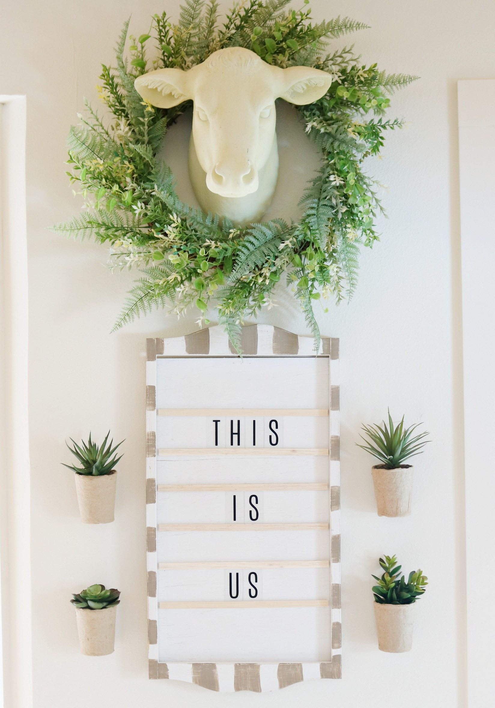 The hanging succulent plants on the wall compliment the neutral decor.