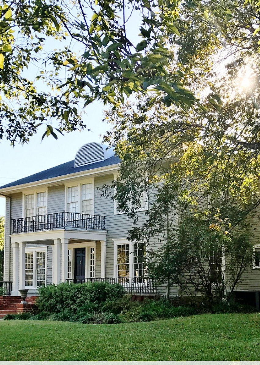 This charming farmhouse has red brick front steps and classic white windows.