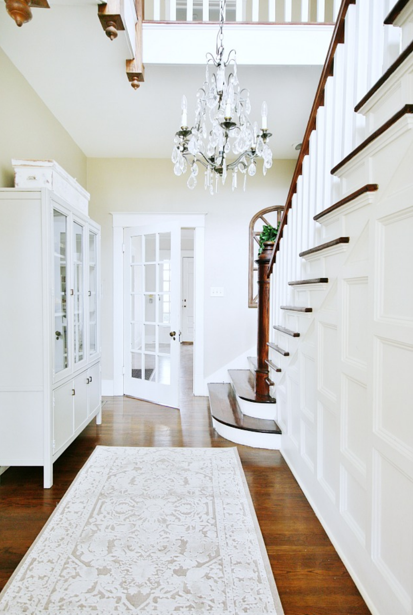 This bright farmhouse entryway features white and wood contrasting elements.