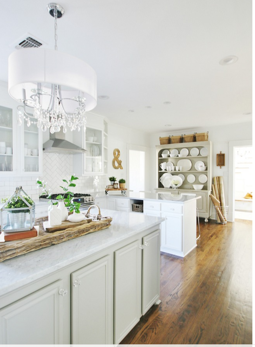 This elegant kitchen has a lot of natural light and white elements to compliment each other.