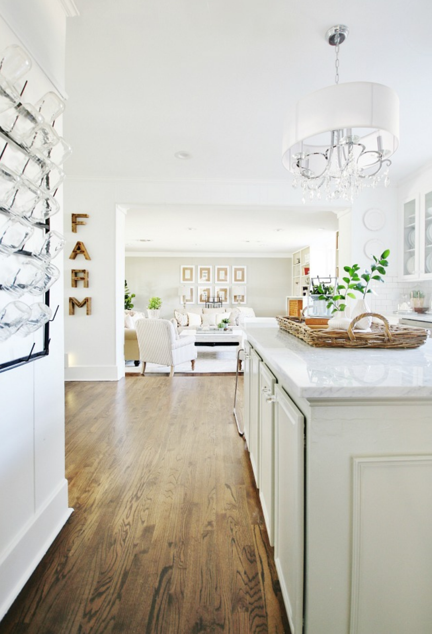 This open kitchen has cute elements like a farm sign and mason jar wall cup holder.