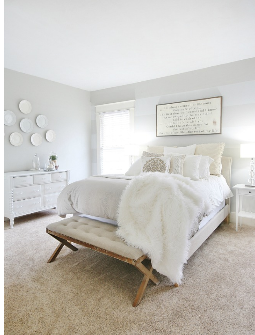 The throw pillows and cozy, fur blanket make this bedroom feel cozy.
