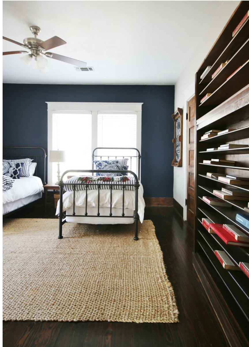 The navy color walls in this guest room compliment the dark stained wood floors.