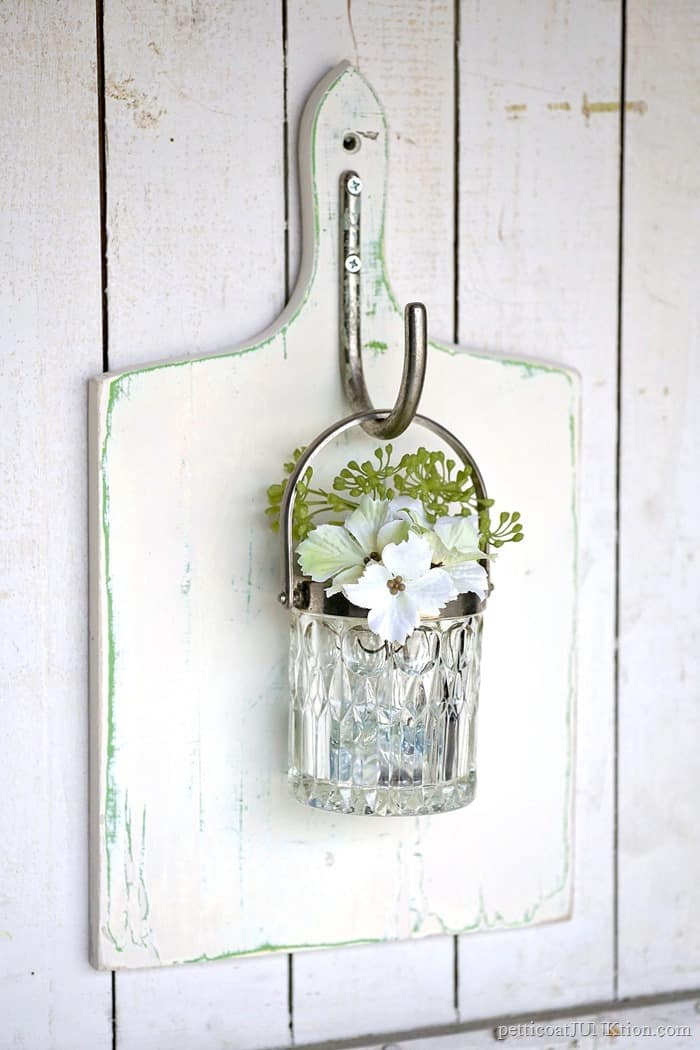 The silver bucket pairs well with this distressed white outdoor decor piece.