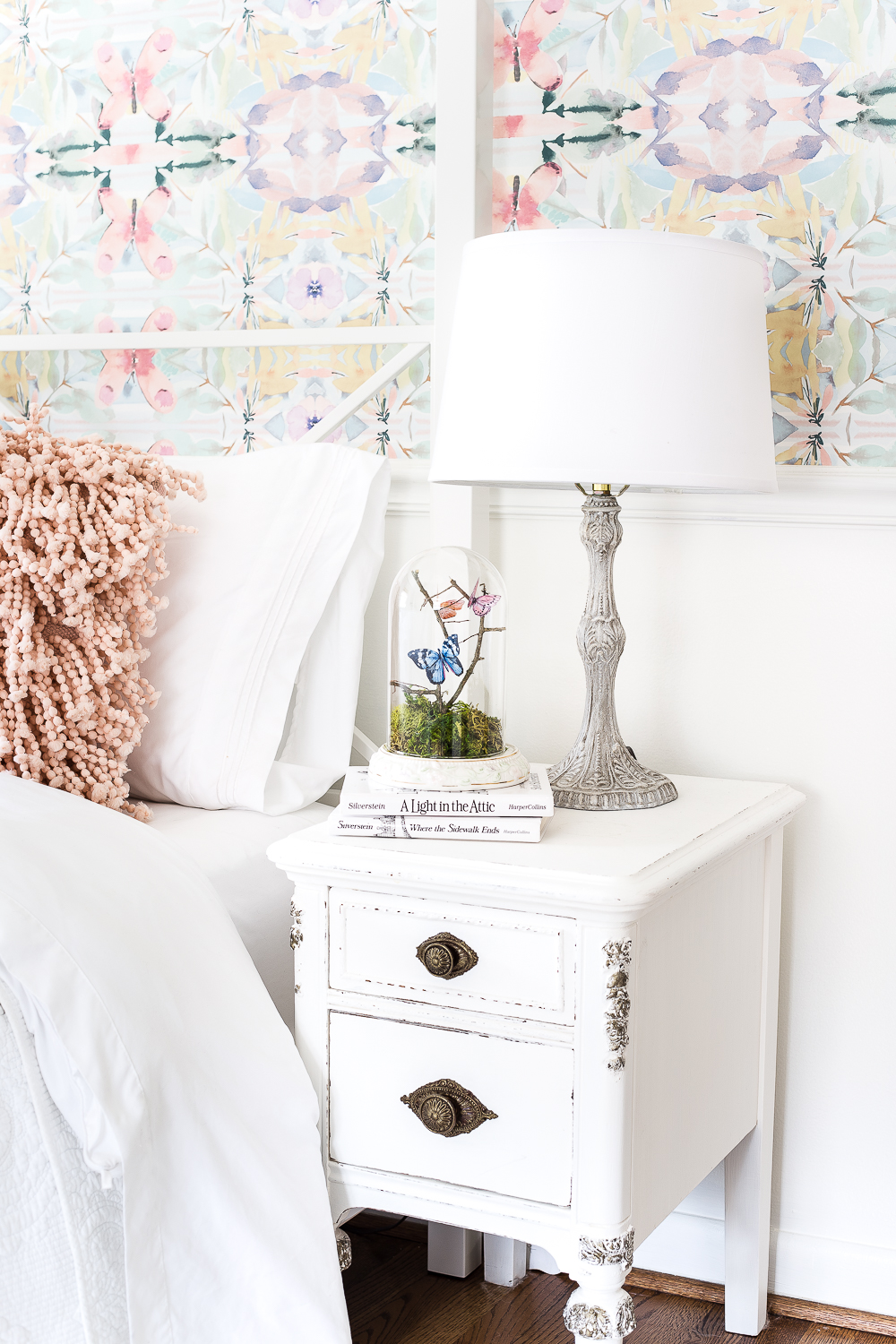 This bright floral wallpaper compliments the white vintage bedside table.