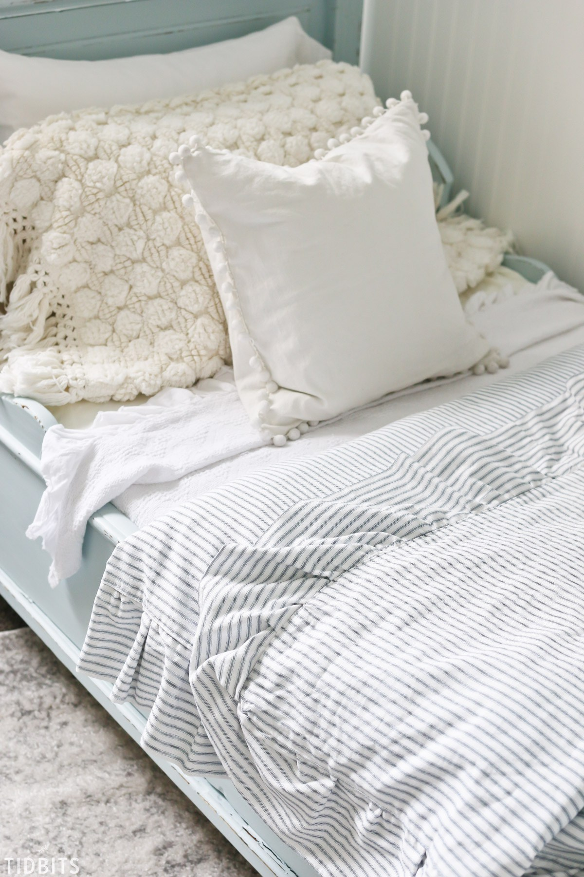 So many textures in this bed spread - I love the knitted blanket and striped comforter