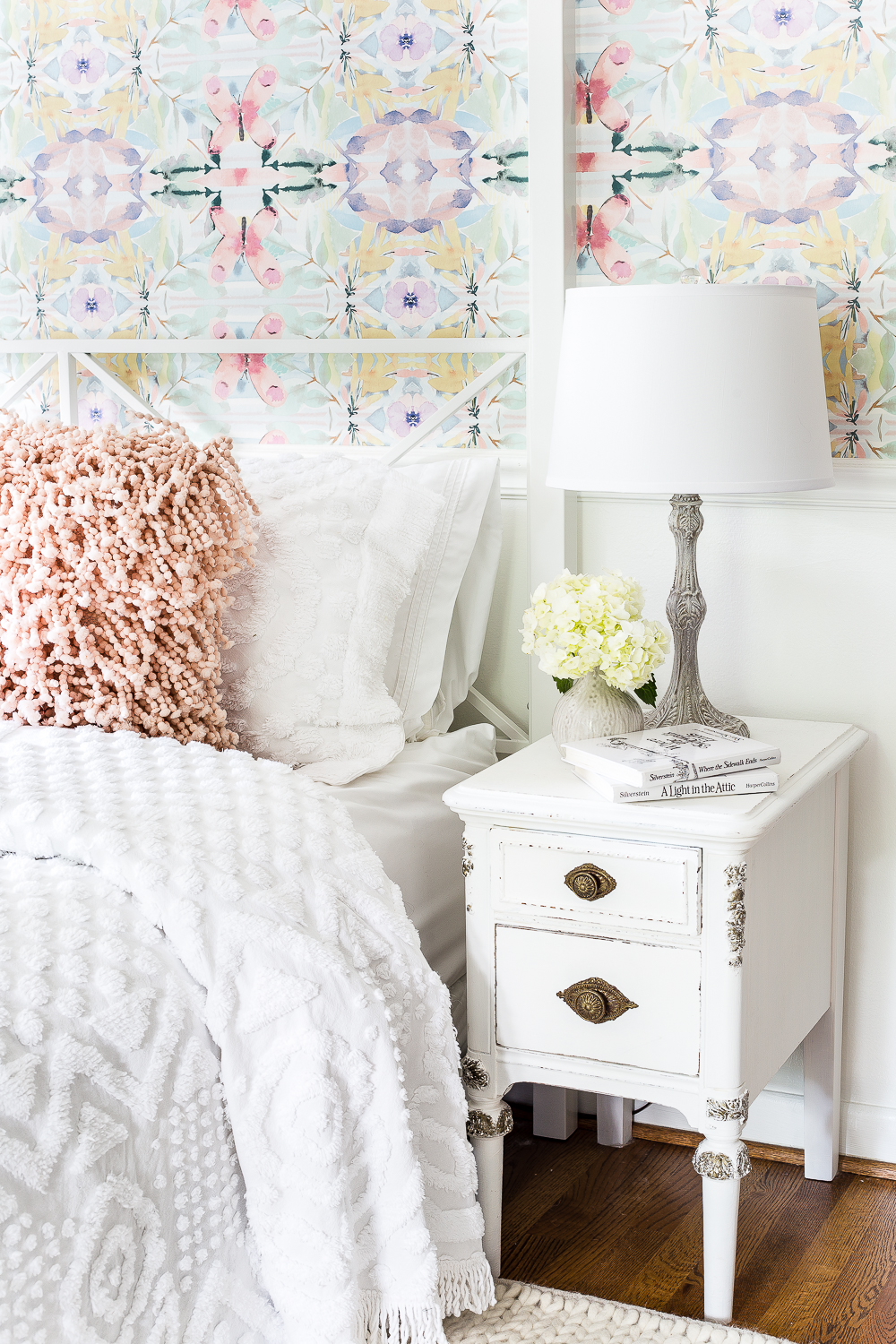 This farmhouse style bedroom is complete with this cute whitewashed bedside table