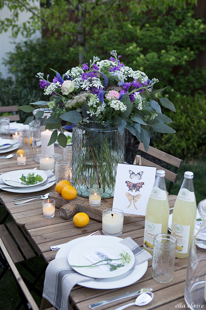 This tablescape is country chic with a gorgeous purple flower centerpiece and lavender table settings