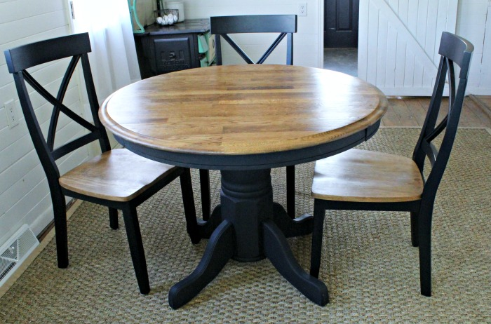 This renovated kitchen table and chairs are sleek with black paint and stained wood.