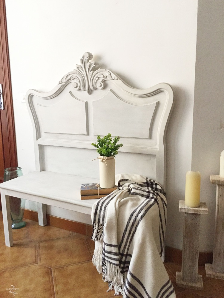 This re-purposed vintage headboard painted white is antique and compliments the tile floor.