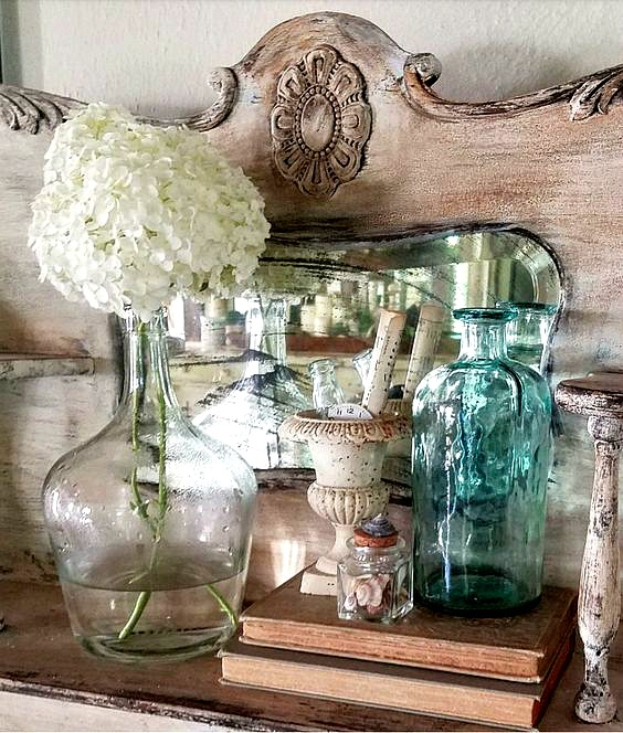 this farmhouse style dresser is decorated with gorgeous vases and vintage books