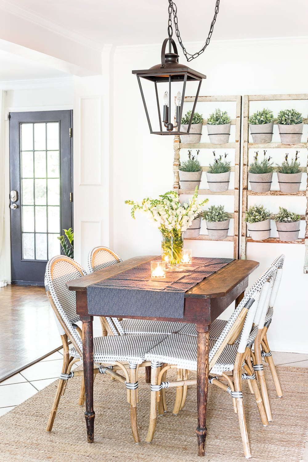 this bright farmhouse style kitchen has planter art on the walls and a vintage lantern overhead light