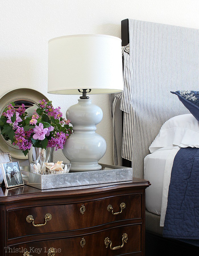 this bedside dresser is decorated with a vintage serving tray and gorgeous purple flowers