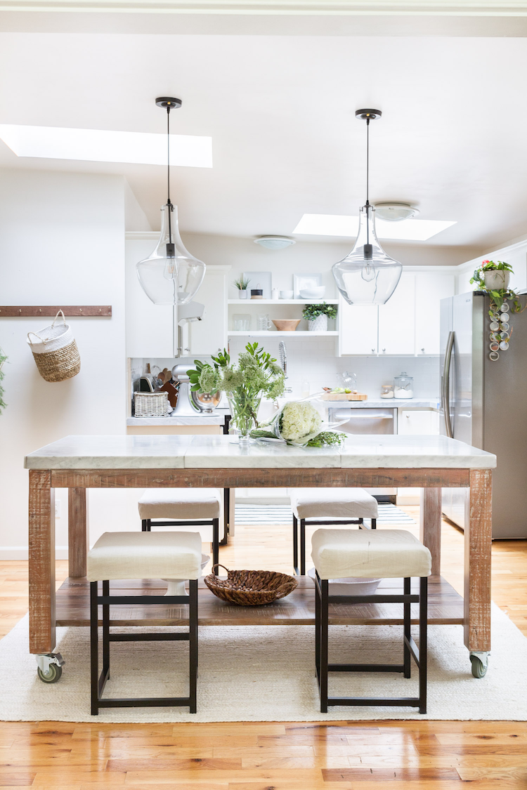 this stunning farmhouse style kitchen's centerpiece is the wooden marble top dining table and quaint farmhouse accessories