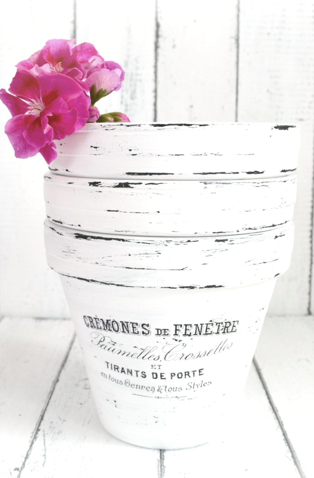 This french inspired flower pot with chipped white paint is rustic.