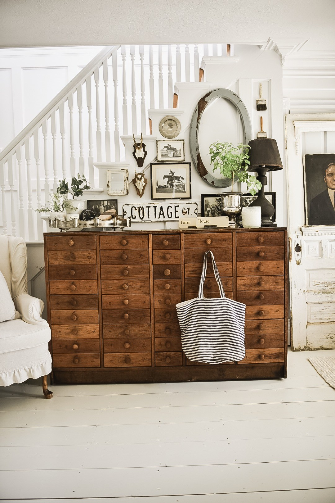 This rustic farmhouse style gallery wall has so many stunning elements, like the centerpiece storage cabinet