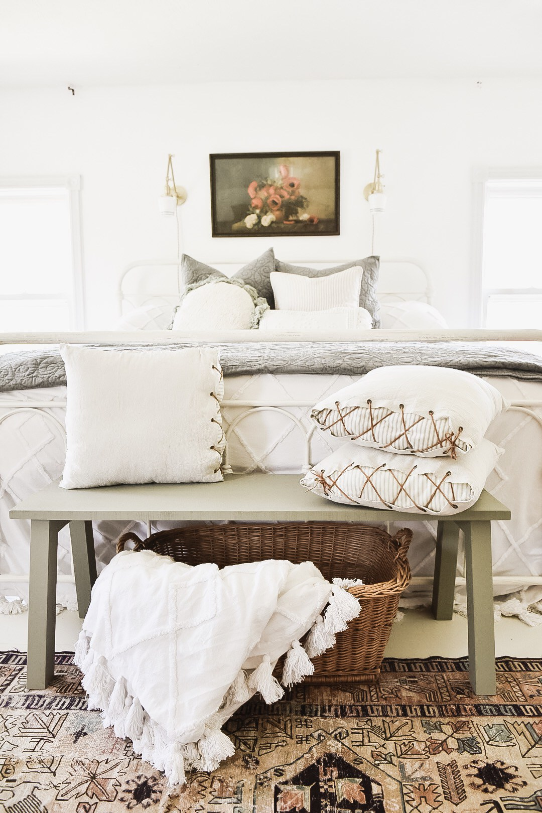 These unique throw pillows and patterned rug add to the white tones in this farmhouse bedroom.