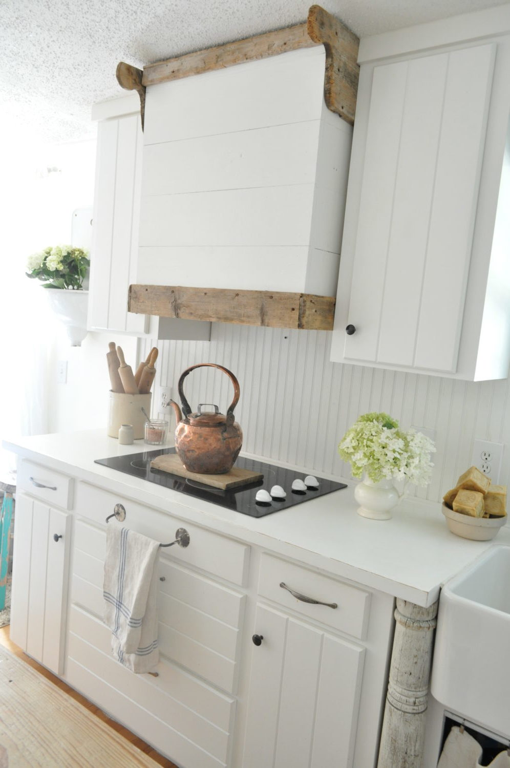 The wood accents in this kitchen against all the white cabinets works well.