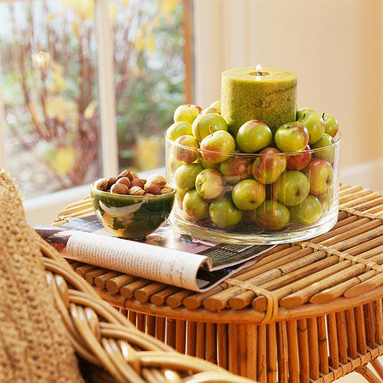This DIY fall centerpiece made with several green apples and a large candle is festive.