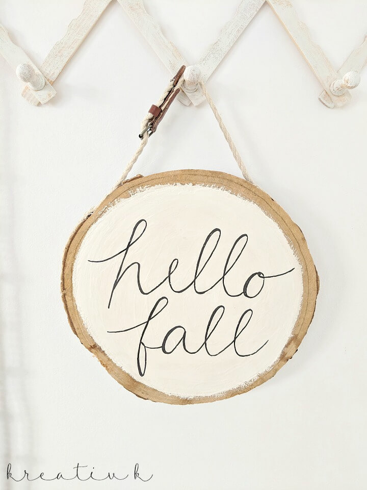 This DIY hello fall sign painted on a piece of wood is rustic for autumn.