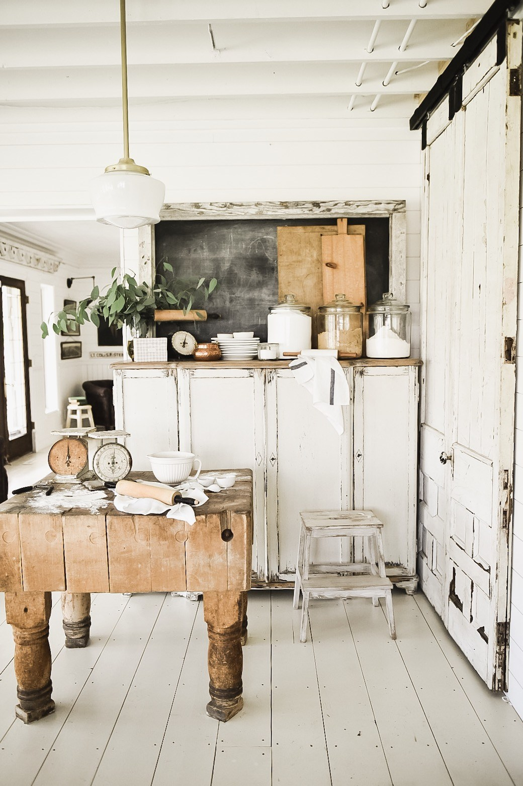 The rustic and weathered wood and sliding barnwood door gives this farmhouse style kitchen a genuine look