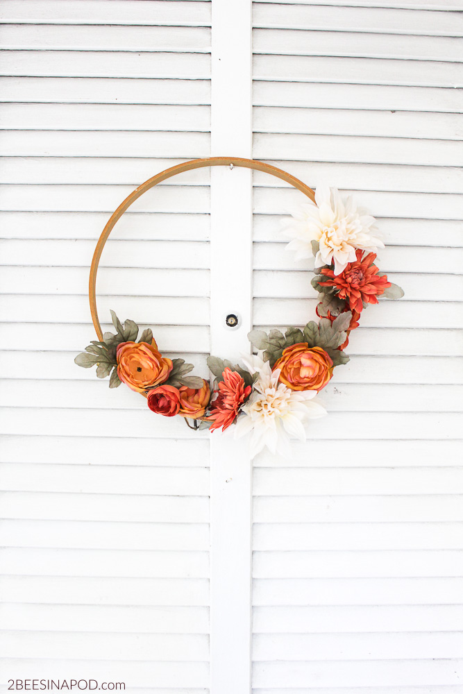 This classic fall wreath with simple flowers and a wood base pairs well against the white shutters.