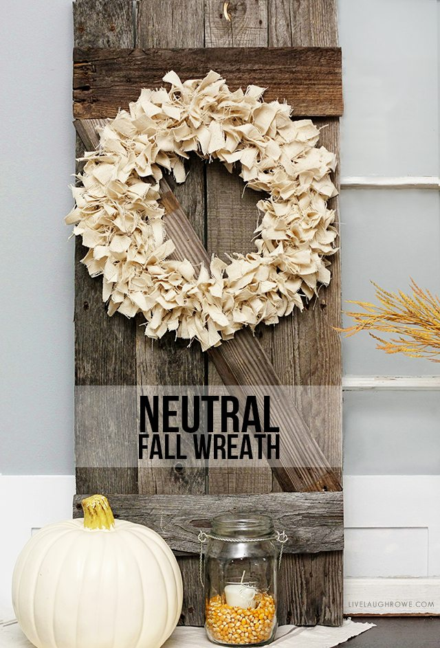 The look of this neutral fabric fall wreath pairs well with the rustic wood.