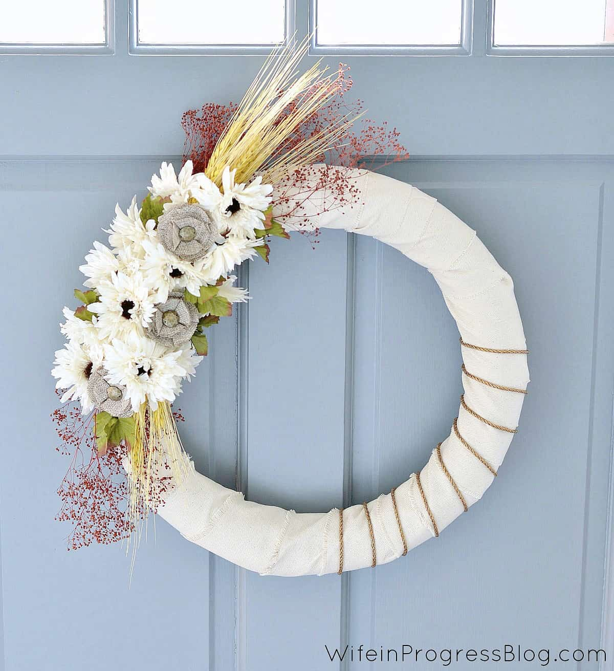 This simple DIY wreath with fresh flowers and gold ribbon is cute.
