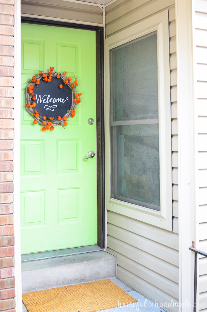 The orange flowers on this DIY wreath pair well with the bright green front door.