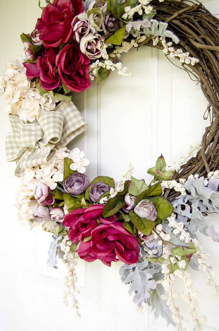 The hot pink roses on this DIY wreath look great with the plaid ribbon.
