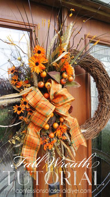 This DIY fall wreath with orange ribbon, orange daisies, and rustic sticks is perfect for autumn.